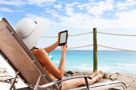 electronic book: Beautiful young woman sitting on the chair under sun