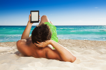 deitado: Homem que relaxa na praia deitado na areia e leitura de e-book no fundo de areia branca