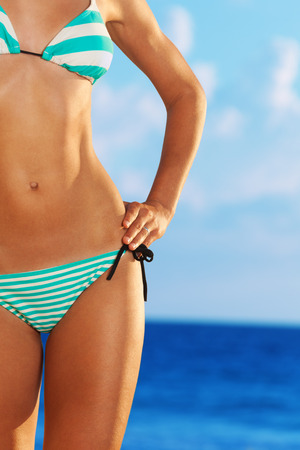 young bikini: Close-up of woman body in bikini with ocean on background
