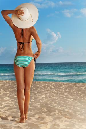 좋은 아름다운 매력적인 여자의 다시 해변에 서서 바다를보고