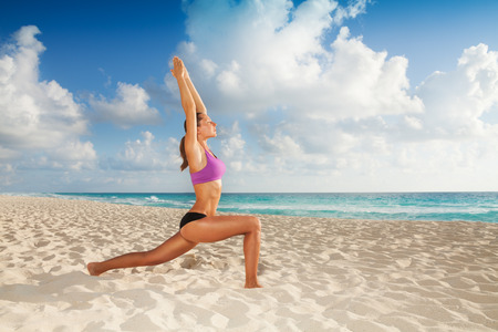 Beautiful attractive young woman exercising yoga on the empty beach in the morning