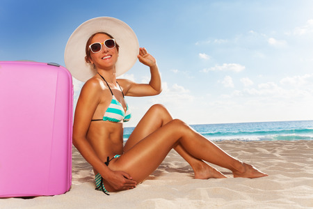 Close portrait of young attractive woman sitting on the beach with cute pink suitcase enjoying the sunshine wearing straw hat photo