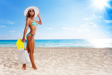 Young attractive woman walking to the ocean with beach bag and snorkel fins wearing straw hat and shades photo