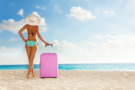 Beautiful tall woman with big pink suitcase standing on the white sand beach photo