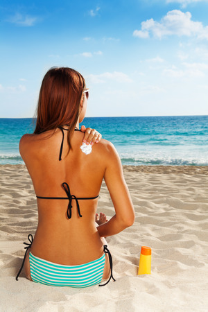 sunbath: Back of gorgeous young woman applying sun protection on tanned skin sitting on sandy beach Stock Photo