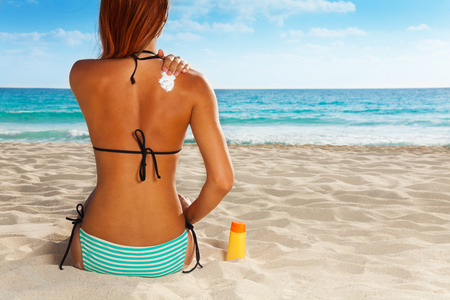 Ð¡ute girl sitting on sandy beach applying sunscreen on her back Stock Photo