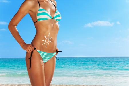 Nahaufnahme der jungen Frau, die am Strand in blau gestreiften Badesachen und niedliches Zeichnen Sonne auf den Bauch von Sonnenschutzcreme gemacht