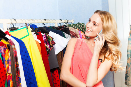 Young woman talking with mobile phone near row of clothes in the shopping mall photo