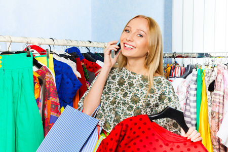 Young woman talking on mobile phone and holding chosen clothes in the shop photo