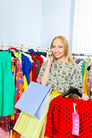 Young happy woman talking on mobile phone and holding chosen clothes in the shop photo