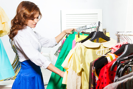 Beautiful young woman choosing clothes in shop which are hanging in a row