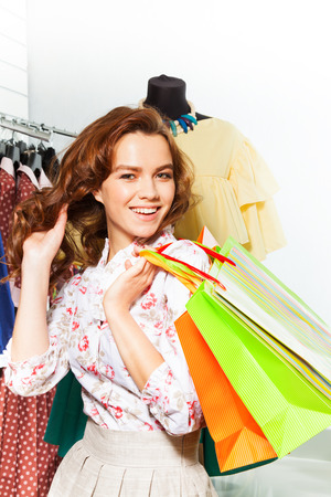 Smiling happy girl carrying colourful shopping bags in shopping mall photo