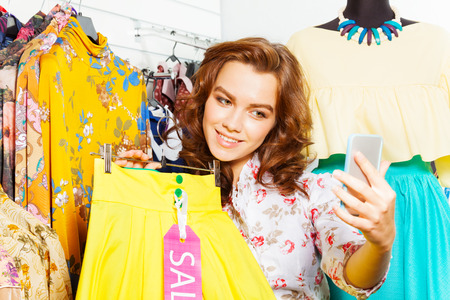 Beautiful woman making photo with mobile in shop while holding yellow skirt in her hand photo