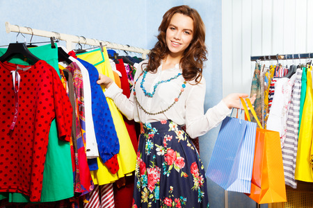 choosing clothes: Charming young woman holding chosen clothes with shopping bags in mall