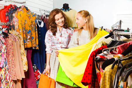 choosing clothes: Two beautiful women choosing yellow skirt in shop