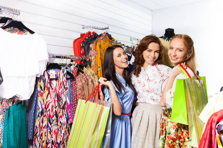 3 happy women with shopping bags in shop photo
