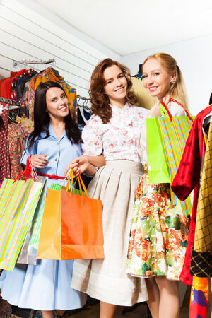 3 smiling women together with shopping bags in shop photo