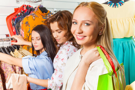 Looking woman straight and her friends in shopping mall choosing clothes photo