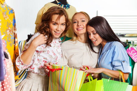 Three young excited women with shopping bags during sale in the mall photo