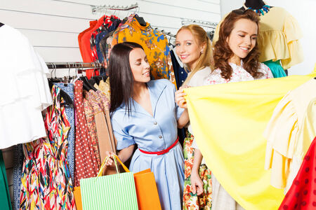 3 happy excited girls with shopping bags choosing clothes in shop photo
