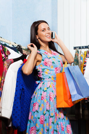 Young woman holding chosen clothes, shopping bags and talking with mobile phone photo