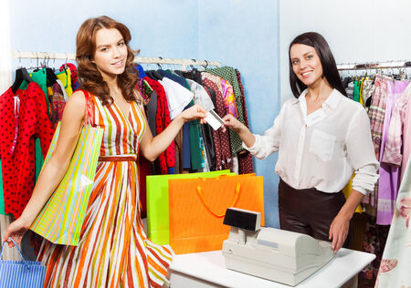 Happy young woman paying with credit card for her purchase in the shopping mall photo