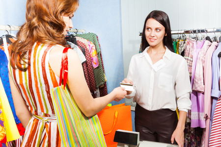 Young woman paying with credit card for her purchase in the shopping mall photo