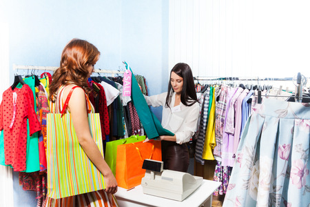 Happy young woman in the shopping mall standing near cashiers desk while shop assistant packs the purchase photo