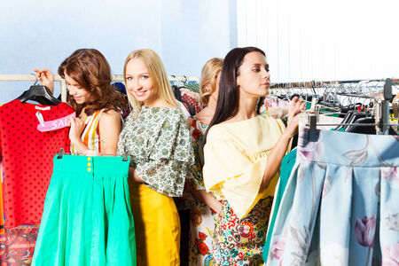 Three women are trying to choose clothes among others in the mall photo