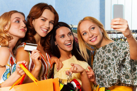 4 smiling girls making photo with mobile camera in the shopping mall photo
