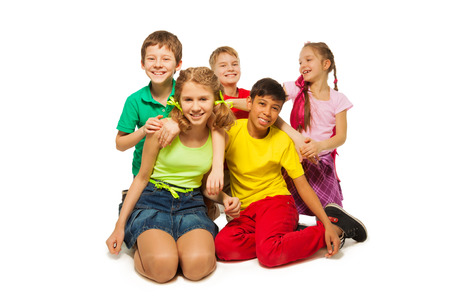 Laughing children sitting on the floor together on the white background photo