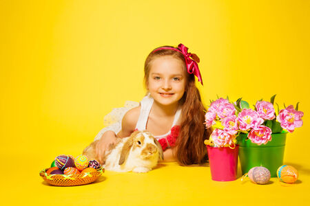 Girl lying on floor with tulips and cute rabbit on the yellow background photo