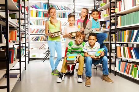 Six pupils together in the library with piles of books photo