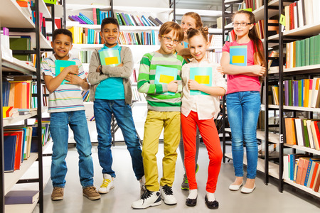 kids reading: Children in library holding exercise books and standing between bookshelves Stock Photo