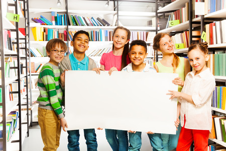 Happy friends standing and holding white paper sheet in library photo