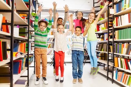 Happy kids jumping with hands up in the library and standing between bookshelves photo