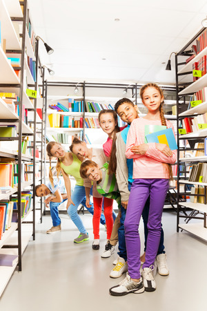 Smiling children standing in a row and playing in library between bookshelves Stock fotó
