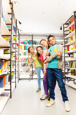 boy book: Four happy kids standing in a row in library and boy in front  holding exercise book Stock Photo