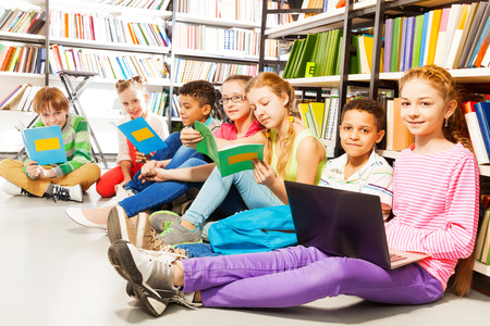 Children sitting on the floor in library and studying holding books Stok Fotoğraf - 28952710