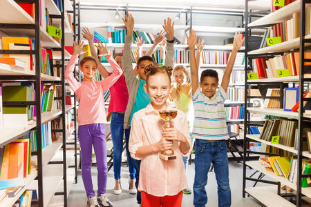 Smiling girl holds golden cup and other kids jumping behind in the library photo
