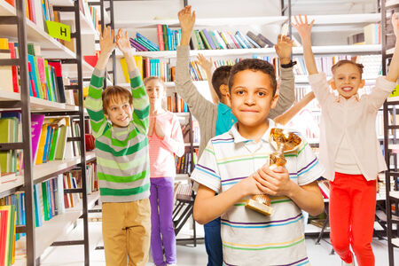 Cheerful boy holds golden cup and other children jumping with hands up behind him in the library photo