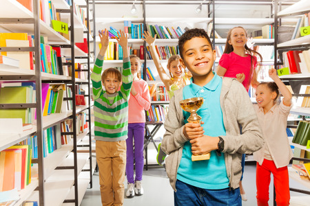 Happy boy holds cup and other kids jumping behind in the library photo