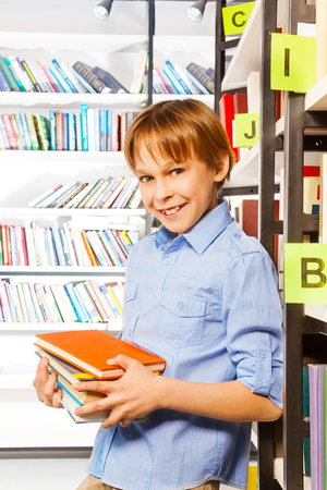 Schoolboy stands and holds books near bookshelf in library photo