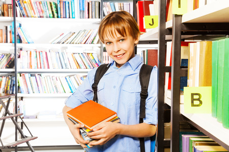 boy book: Smiling cute boy standing and holding books in school library Stock Photo