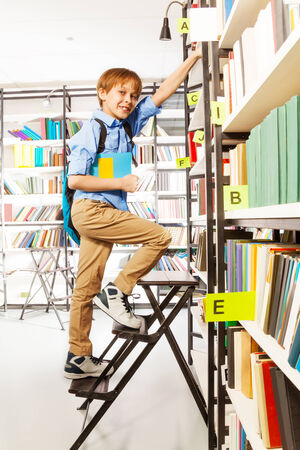 Boy climbing on step ladder in library with blue bag and colorful book