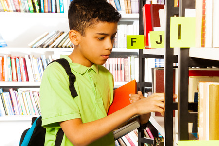 Boy with blue bag puts hand on bookshelf and holds colorful books in library photo