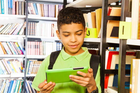 Boy playing with tablet and standing near bookshelf in library photo