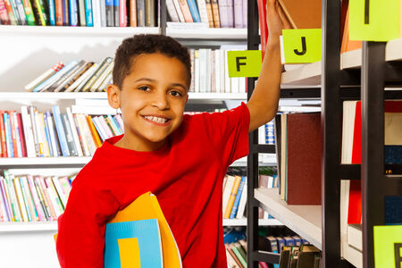 Smiling boy puts hand on bookshelf and holds colorful books in library photo