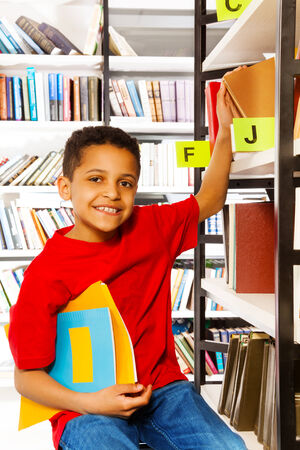 Smiling boy with hand on bookshelf and holds colorful books in library photo