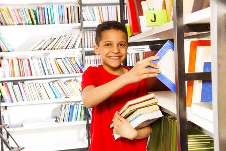 ni�os negros: Ni�o feliz con la mano en el estante tiene muchos libros en la biblioteca